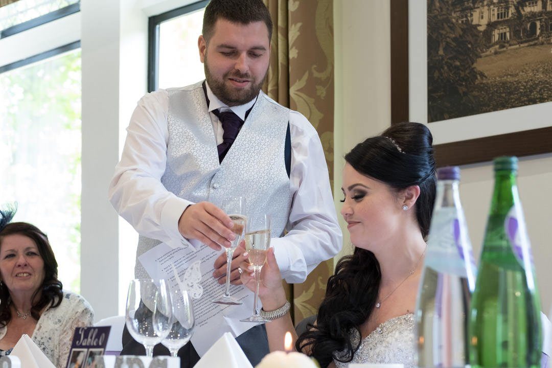 groom toasts the bride with champagne at Frimley Hall hotel during the wedding speeches