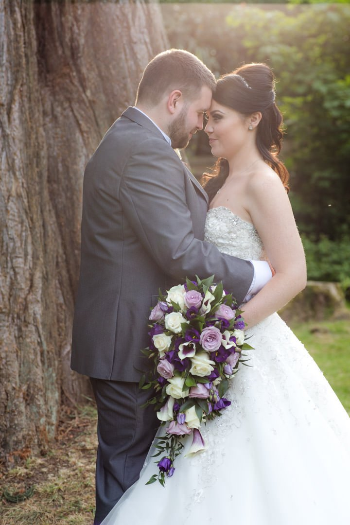 golden hour backlit image of the bride and groom in Frimley Hall hotel gardens