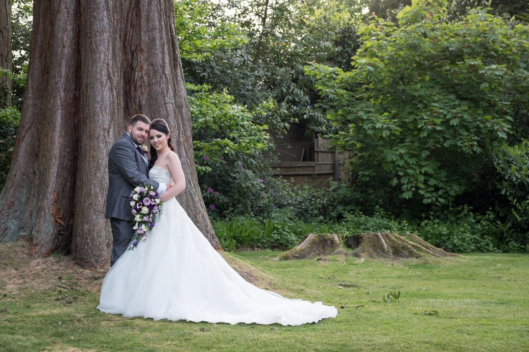 the bride and groom in Frimley Hall hotel gardens