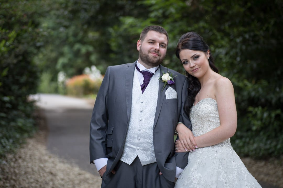 the bride holds the groom's arm at Frimley Hall hotel