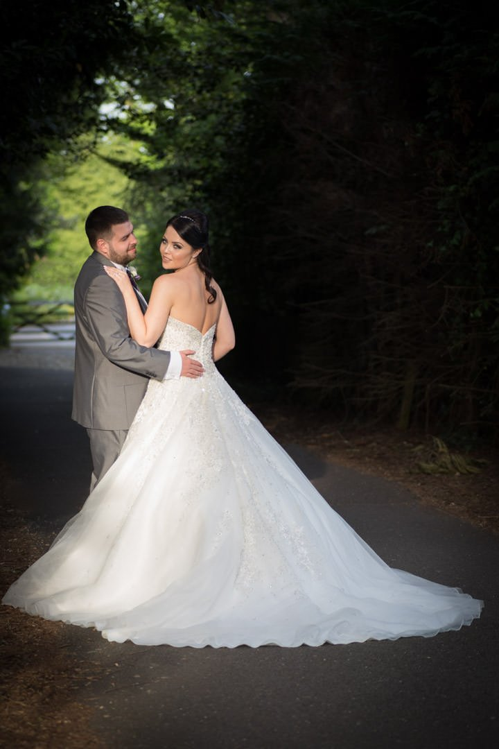 the bride looks over her shoulder and the groom looks at her in a shaft of light at Frimley Hall hotel gardens