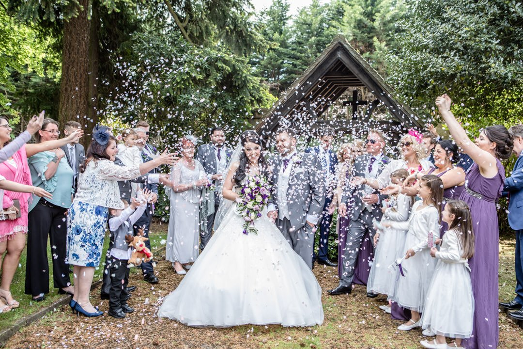full length of the bride and groom in a confetti cloud surrounded by friends at St Andrews Church in Frimley Green