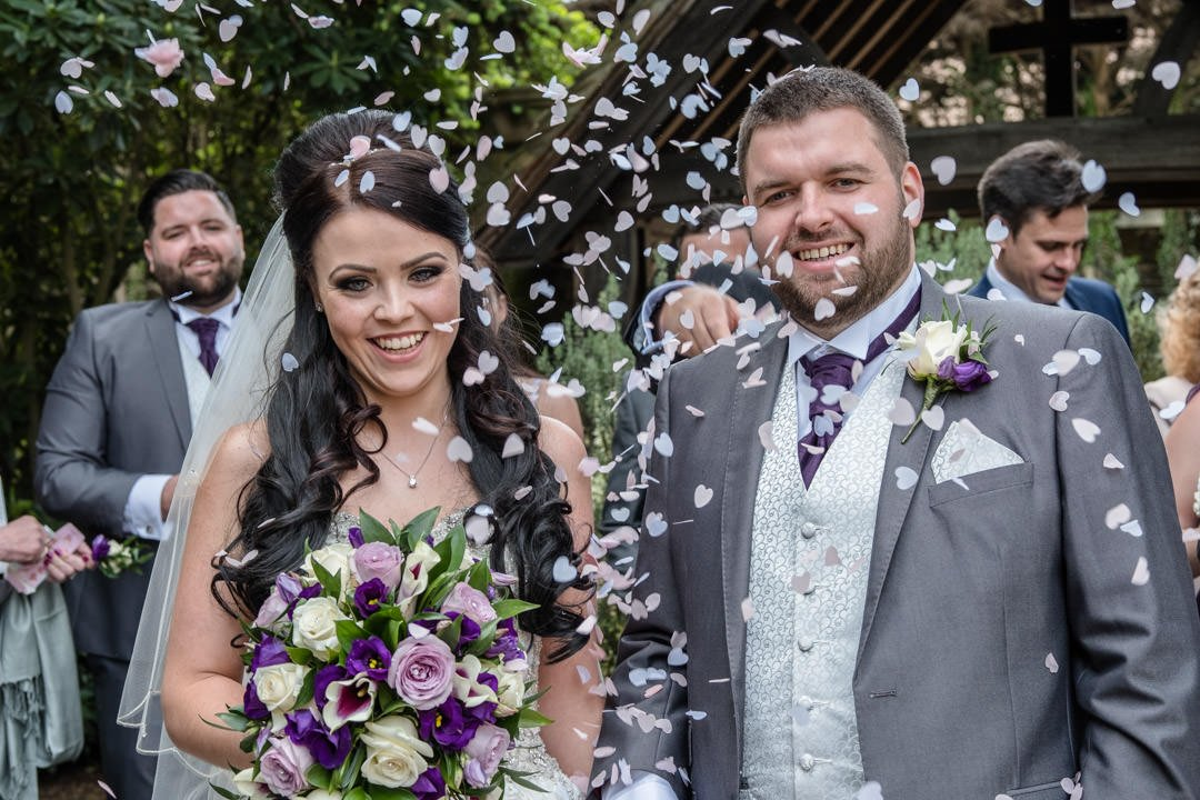 closeup of the bride and groom in a confetti cloud at St Andrews Church in Frimley Green