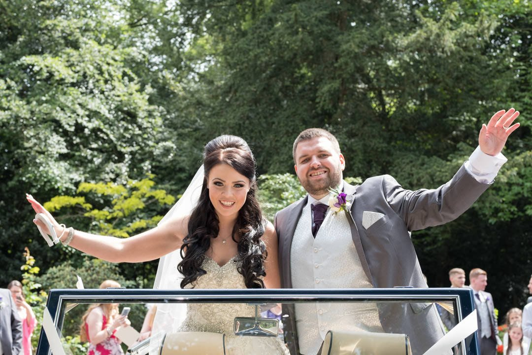 The bride and groom stand and pose in the vintage open top Rolls Royce at St Andrew's church in Frimley Green