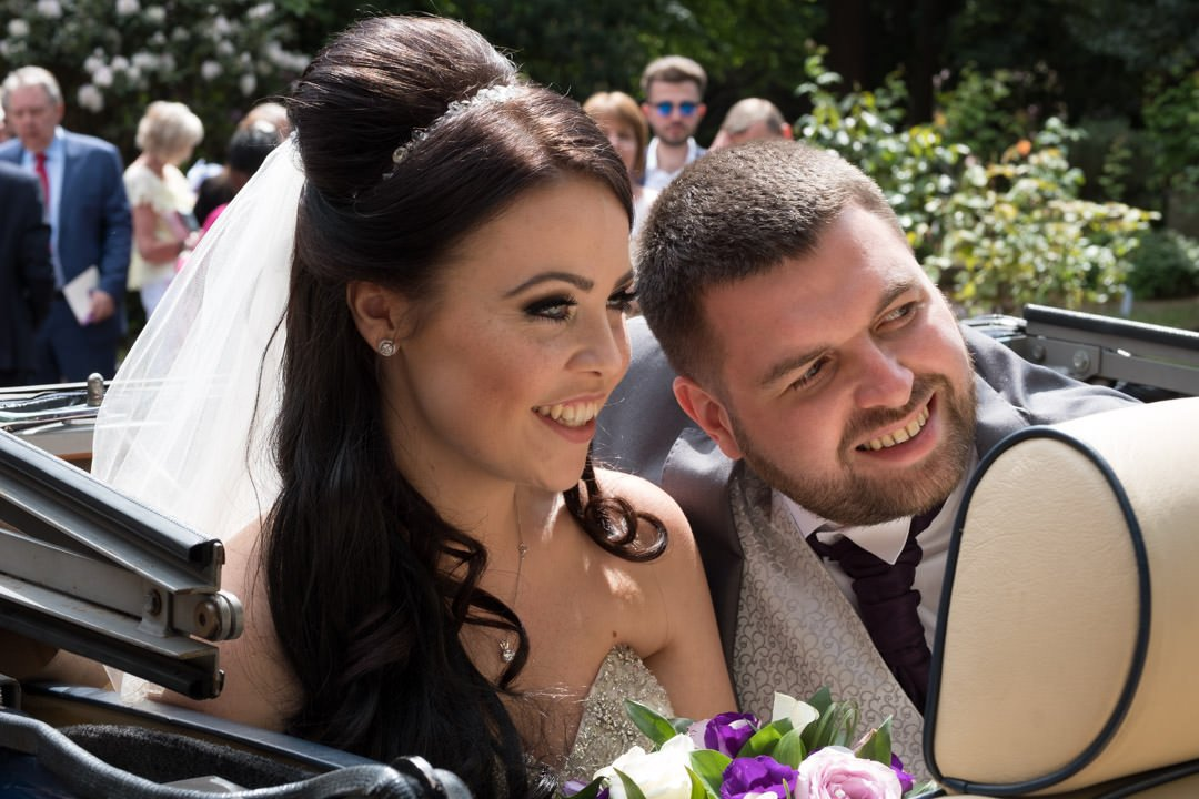 The bride and groom with heads together in the vintage Rolls Royce at St Andrew's church in Frimley Green