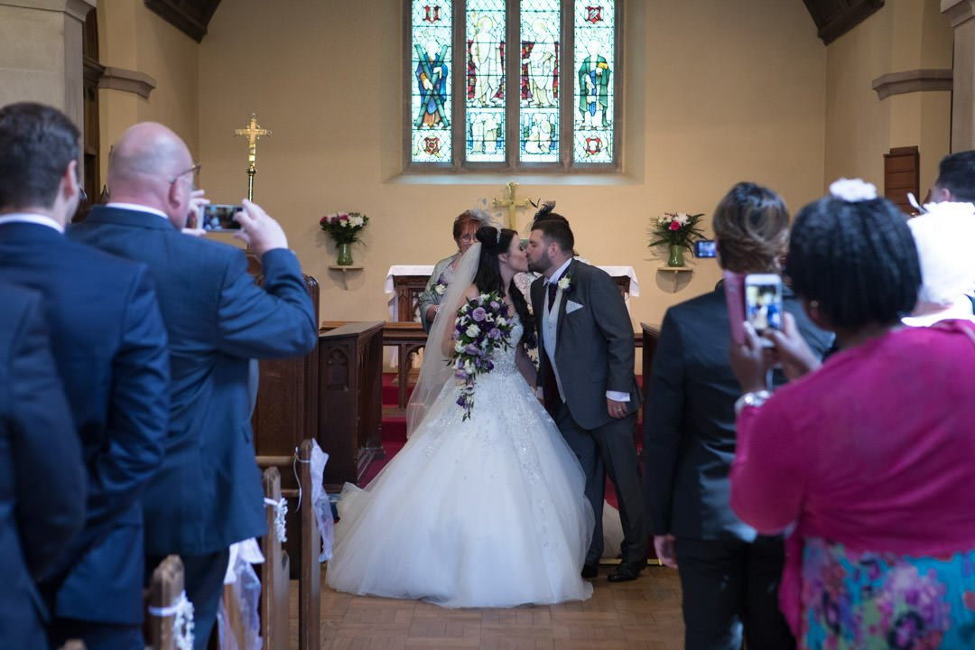 bride and groom kiss at St Andrew's church in Frimley Green