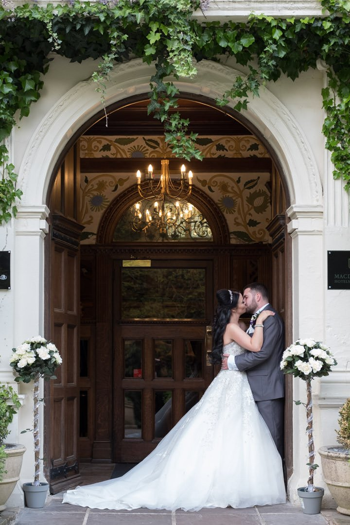bride and groom kiss in doorway of Frimley Hall