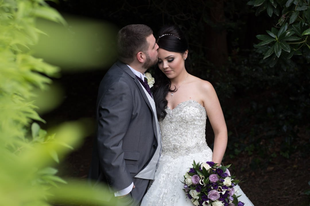 The groom kisses the bride's forehead in the gardens at Frimley Hall Hotel