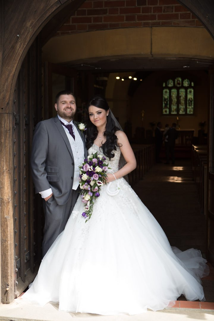bride and groom pose outside the church door of St Andrew's in Frimley Green