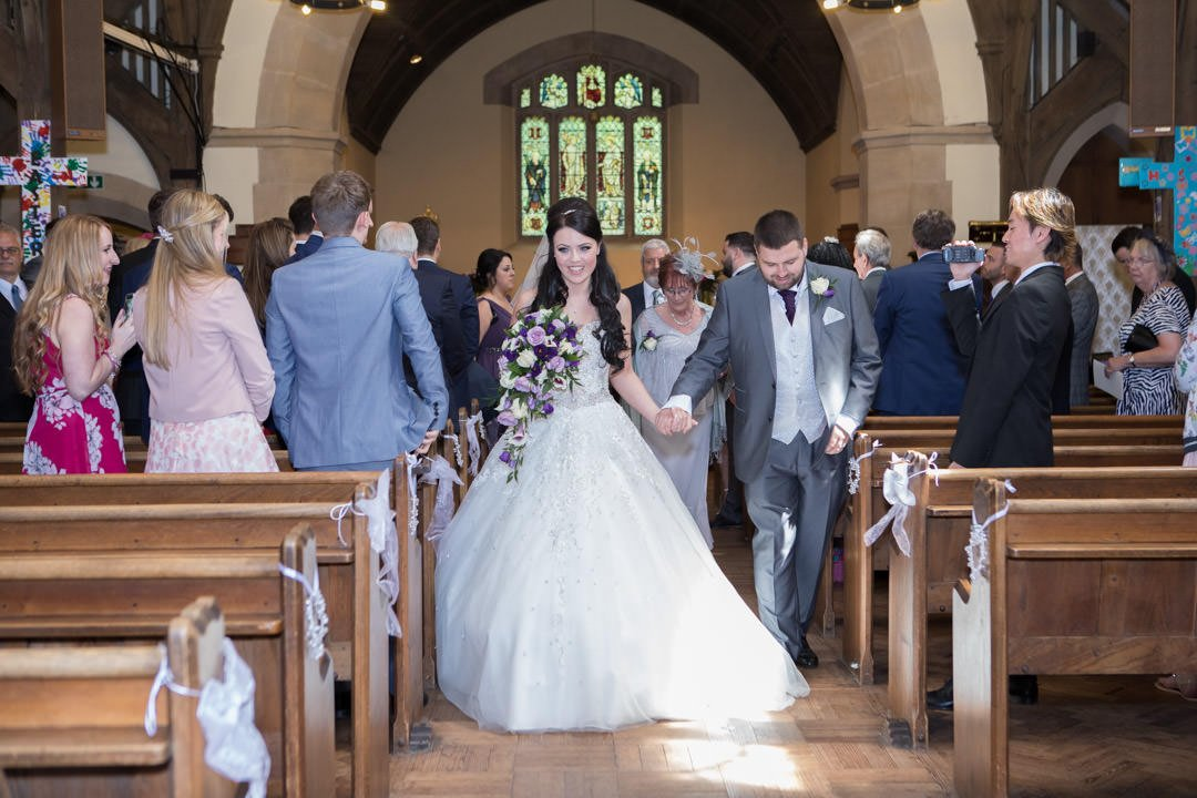 bride and groom walk up the aisle at St Andrew's church in Frimley Green