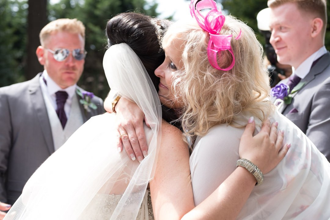 The bride is hugged by one of her female guests wearing a bright pink fascinator