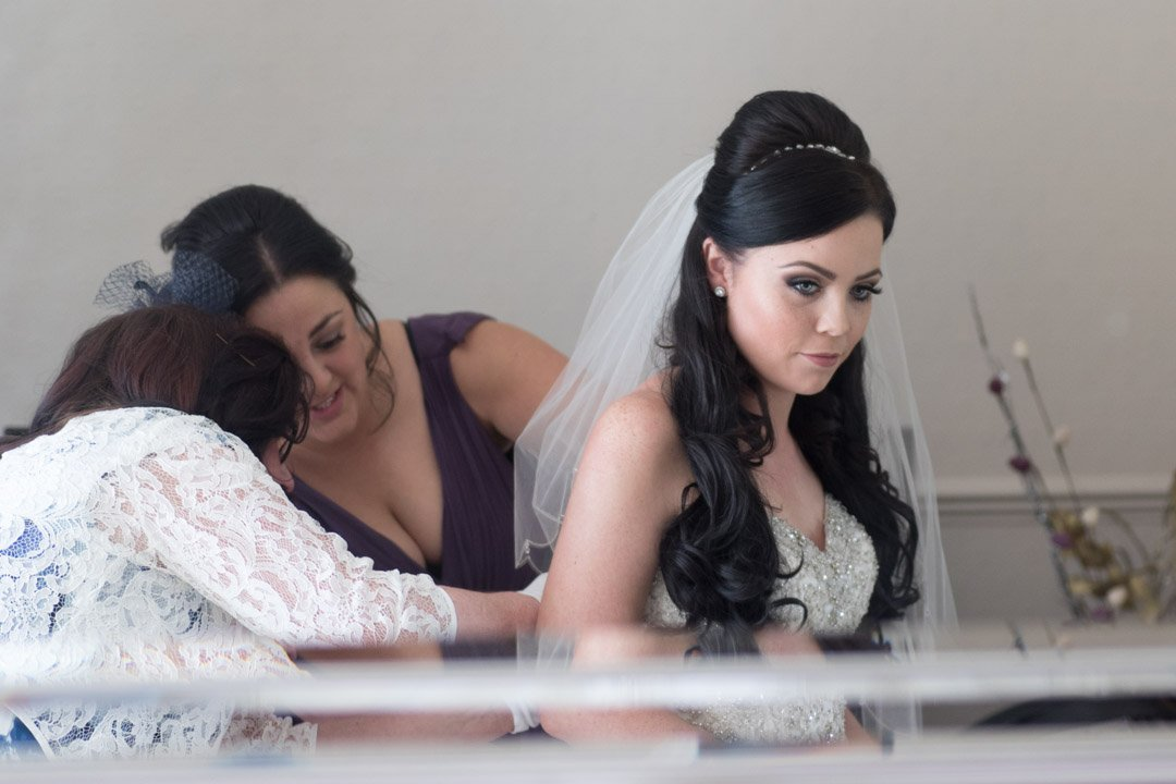 bride looks in the mirror as her dress is buttoned up