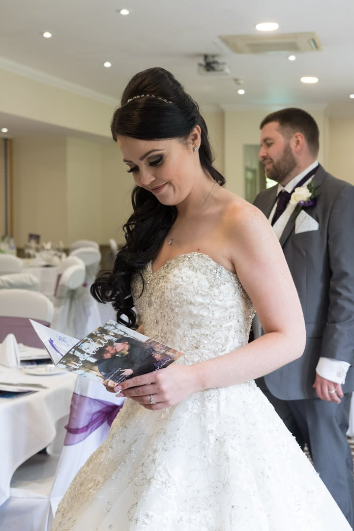 smiling bride looks at her wedition magazine at Frimley Hall Hotel