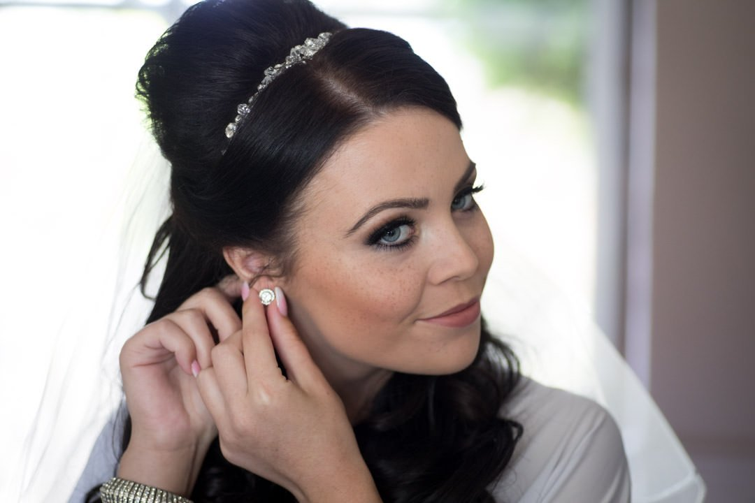 bride puts on her earrings