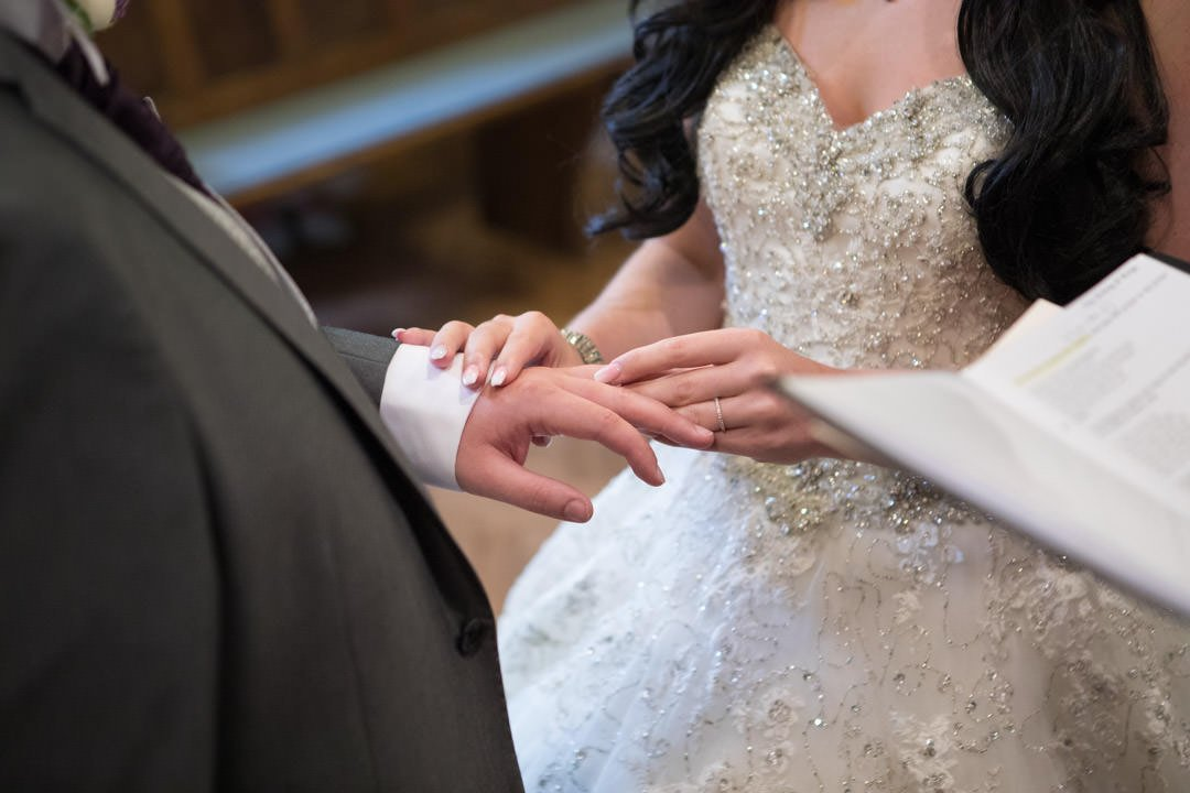 the bride puts a wedding ring on the groom's finger in church