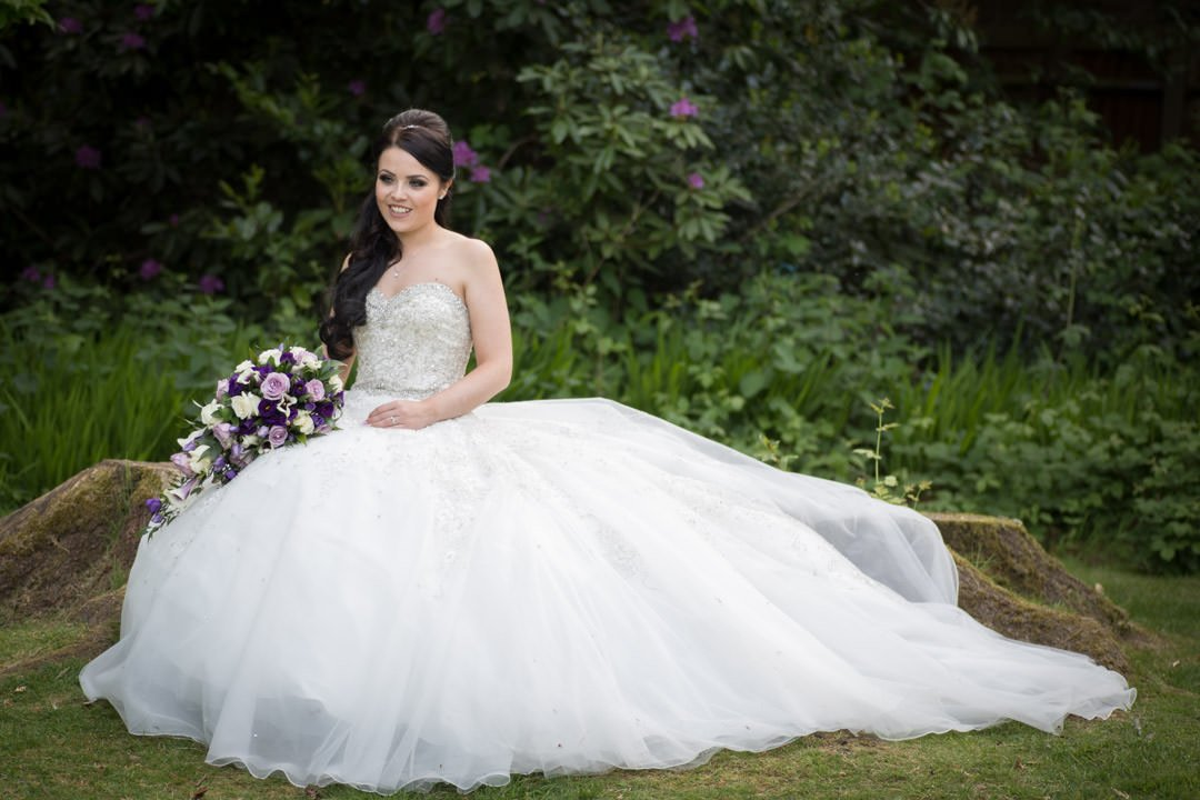 The bride sits in Frimley Hall Hotel gardens holding her bouquet with her wedding dress fluffed out