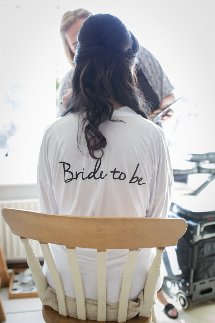 the bride to be sits on a wooden chair wearing a white bride to be dressing gown and has her make up done