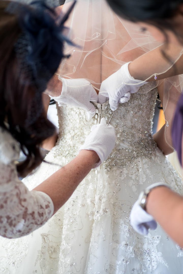 ladies wearing white gloves and using crochet hook button up the bride's diamante and tulle wedding dress