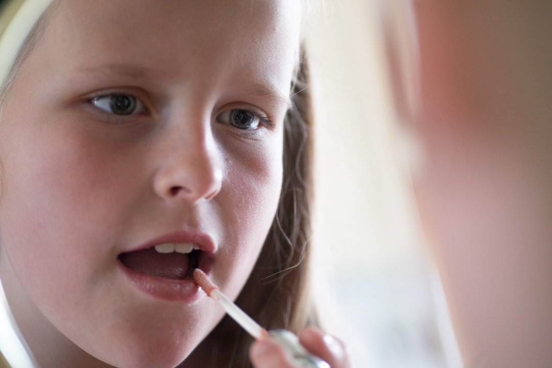 young bridesmaid applies lip gloss in the mirror