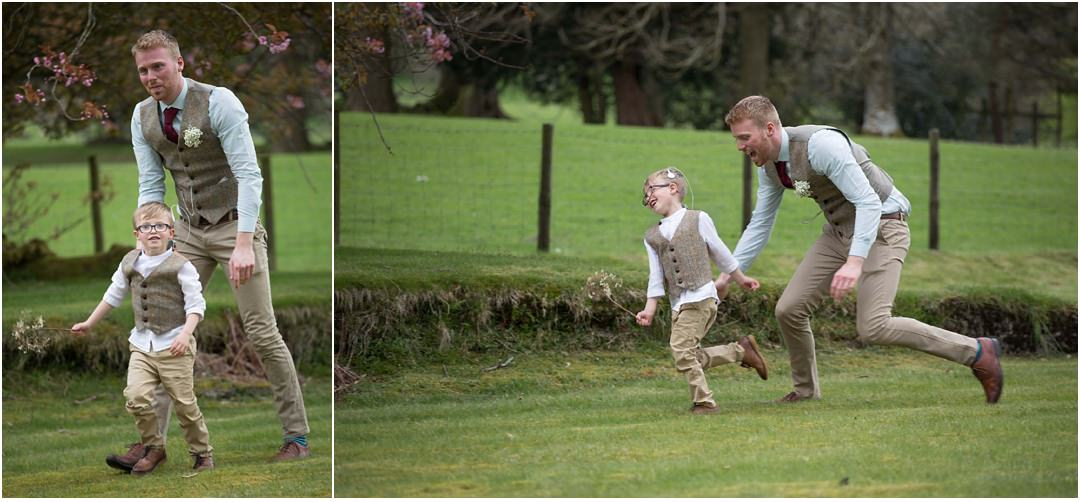 smartly dressed boy and man play outside at the wedding