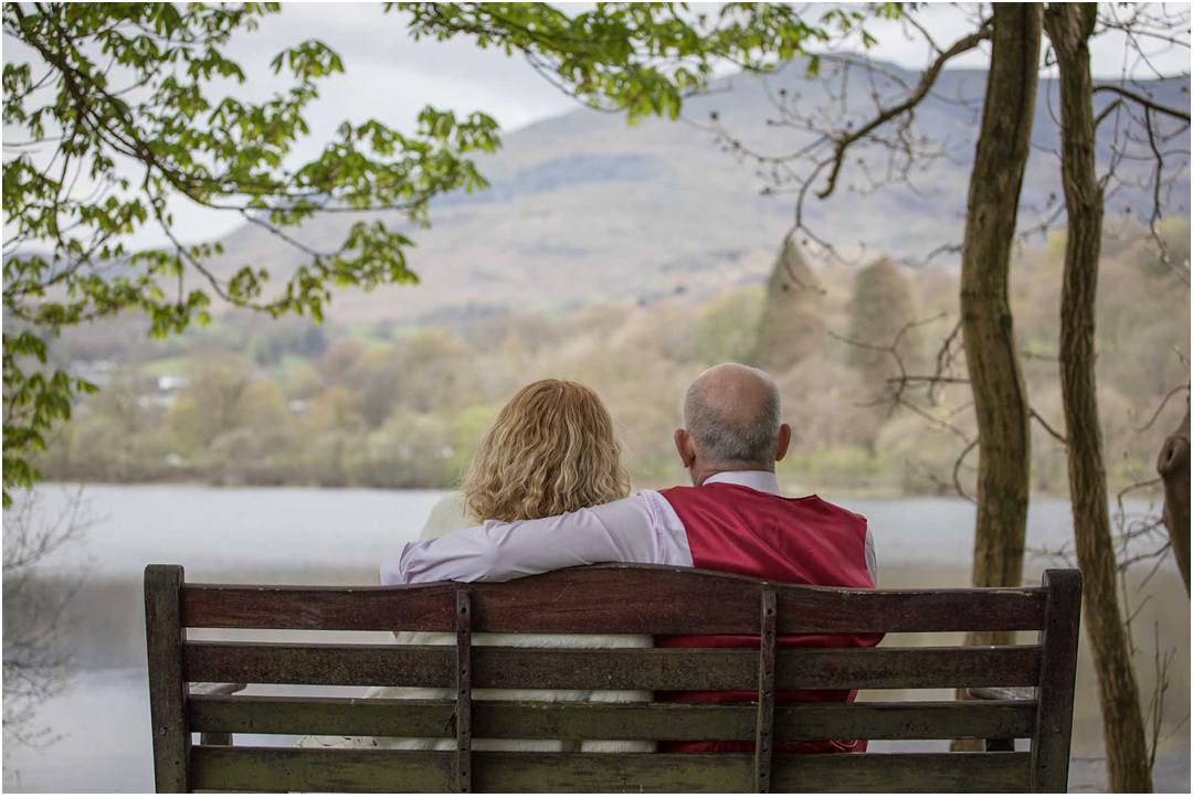The bride and groom sit on a bench overlooking Lake Coniston and Old Man Coniston