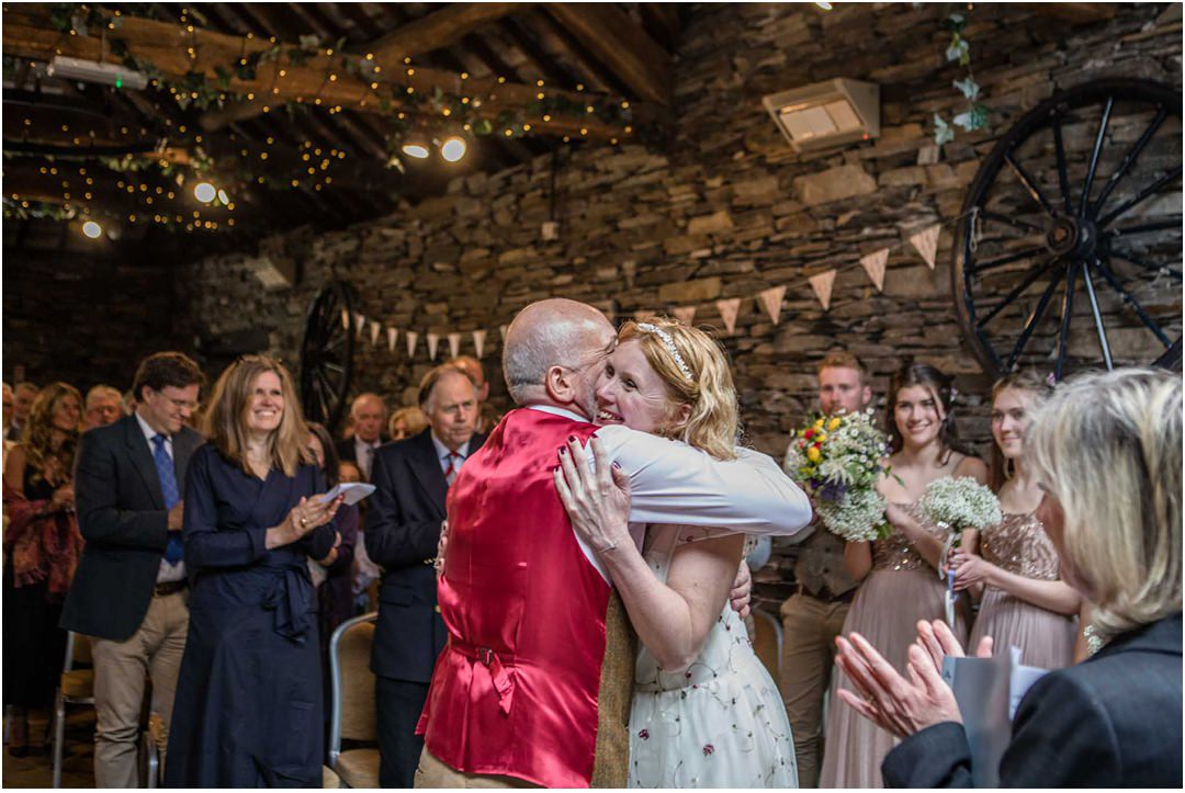 The bride and groom hug each other after the wedding ceremony at Monk Coniston