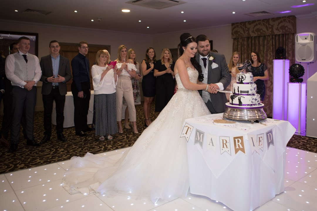 bride and groom cut the cake on the dance floor at Frimley Hall Hotel