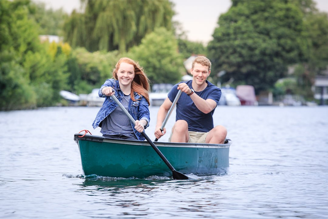 Young engaged couple canoe towards us on the River Thames