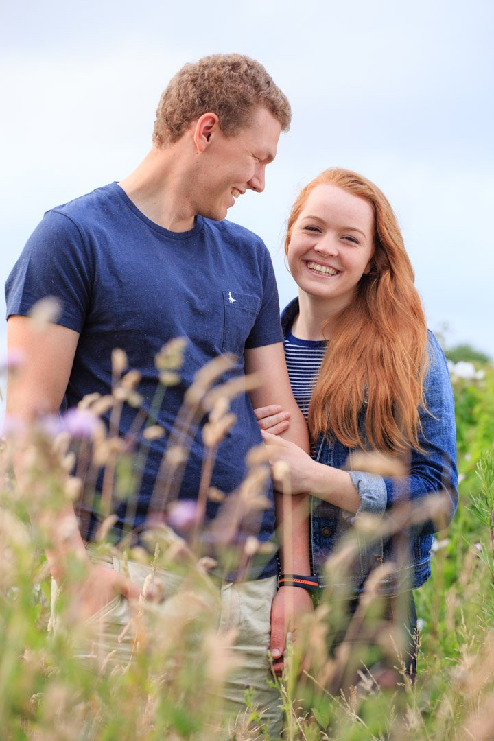 photo of an engaged couple, she looks towards the camera laughing and he looks at her. The view is through long golden grass