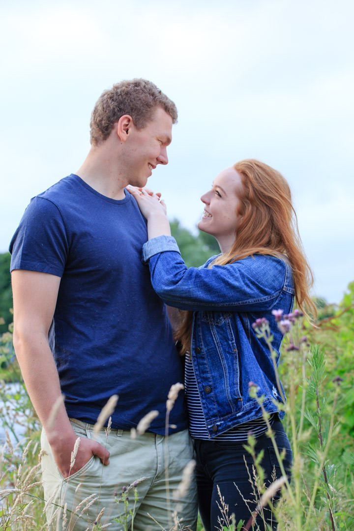 Red headed woman looks up into her fiancé's eyes and they both smile at each other, during their engagement photo session