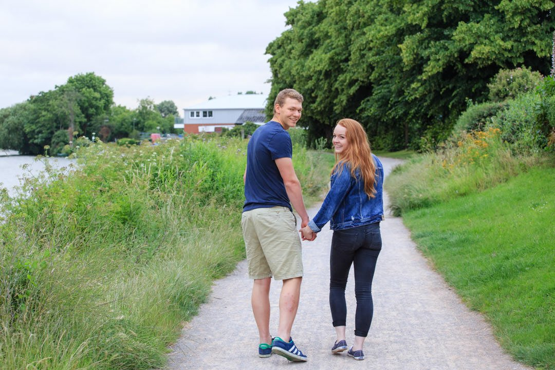young engaged couple turn and look as they walk down the towpath by the River Thames together