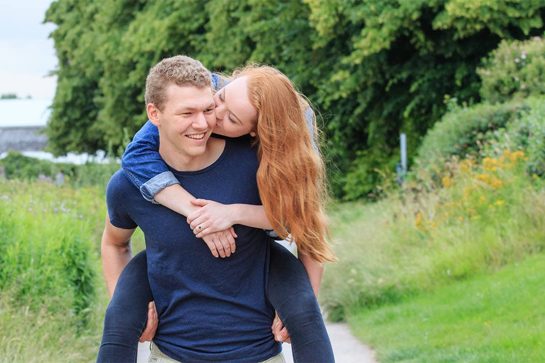 young woman leans to kiss her fiance as he gives her a piggyback, during their engagement photo session on the River Thames towpath near Walton-on-Thames