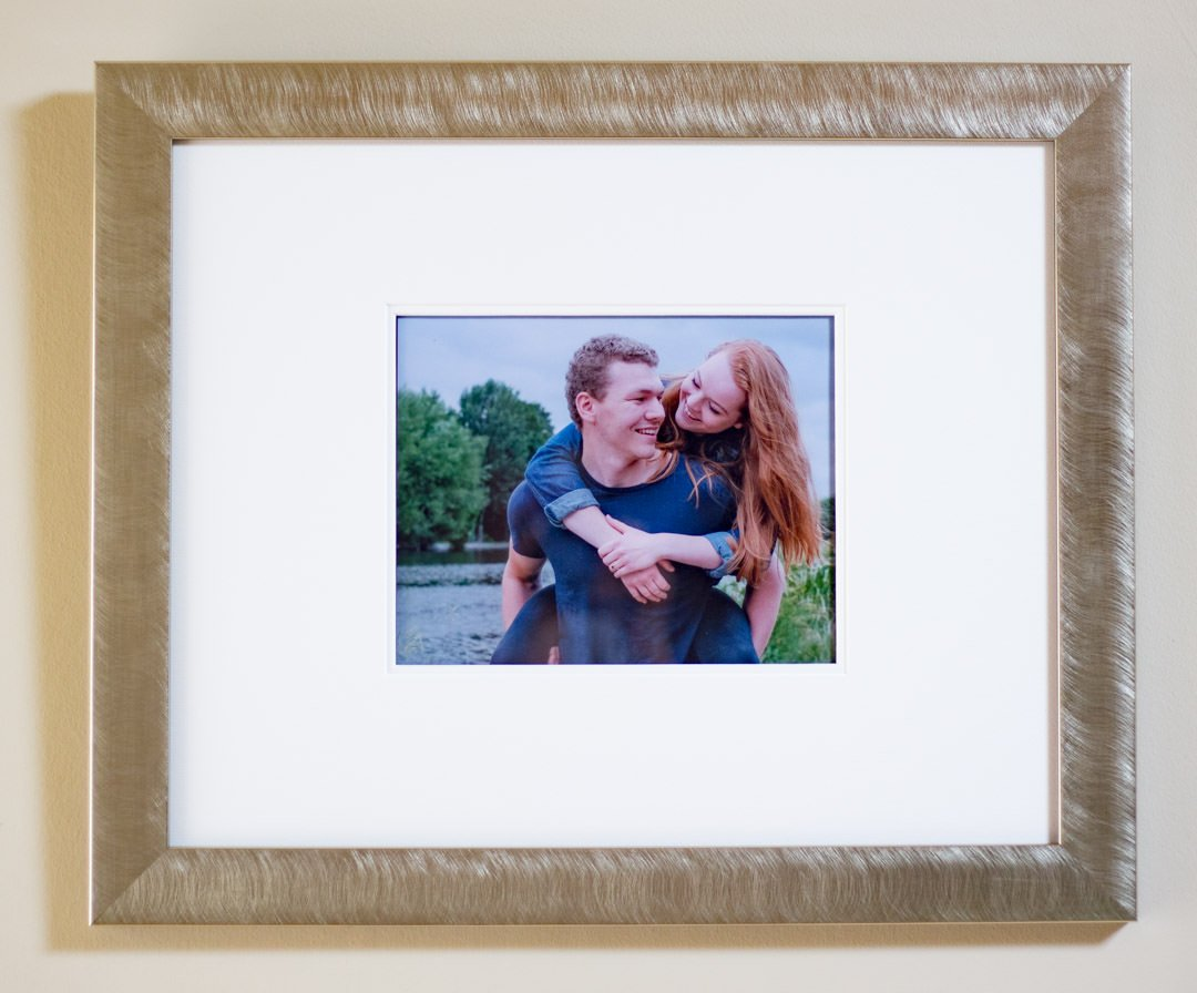 Signing frame for guests to sign at a wedding , that shows the photo of the engaged couple with him giving his fiancee a piggyback