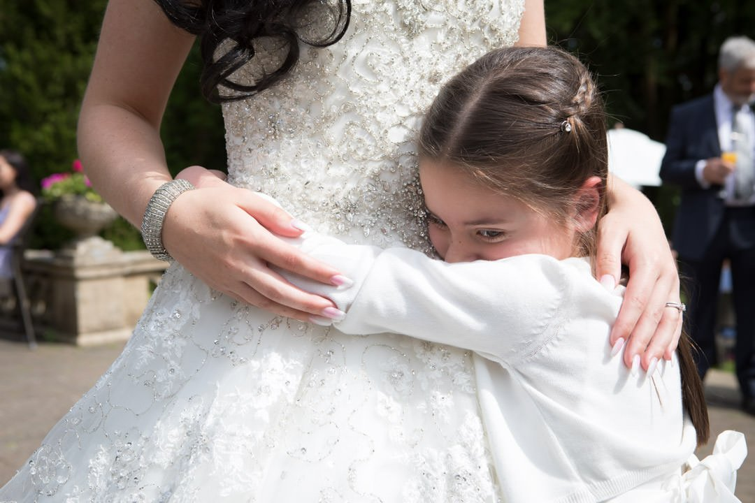 flower girl hugs the bride at Frimley Hall Hotel
