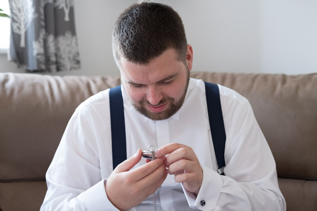 groom looks at his gift of a pocket watch from his bride