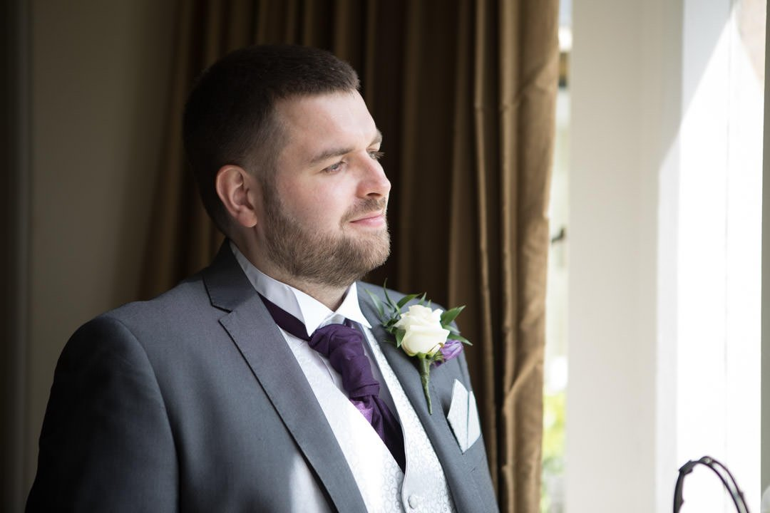 groom portrait looking out of the window in the bridal suite at Frimley Hall hotel