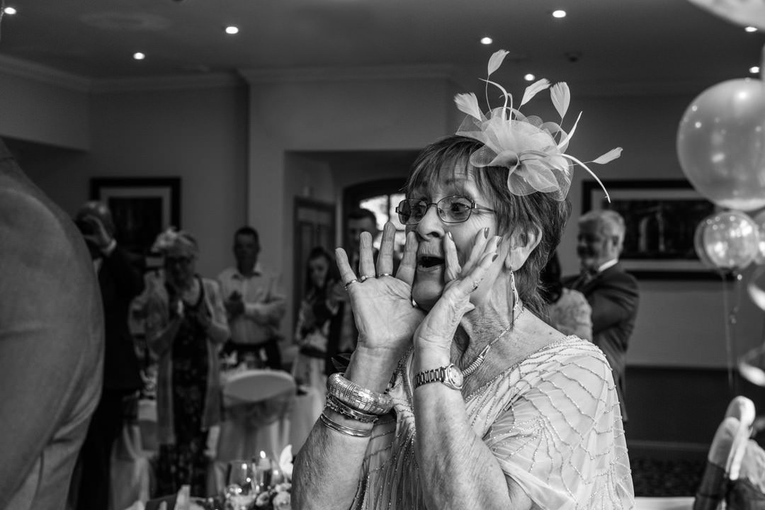 Grandmother's reaction as the bride and groom walk into the Frimley Suite for the wedding breakfast at Frimley Hall Hotel
