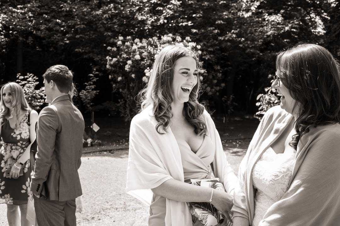 black and white of laughing female wedding guests arriving at St Andrew's church in Frimley Green