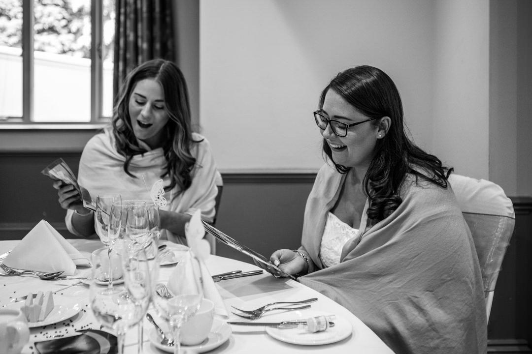 female wedding guests enjoy the wedition magazine at Frimley Hall Hotel