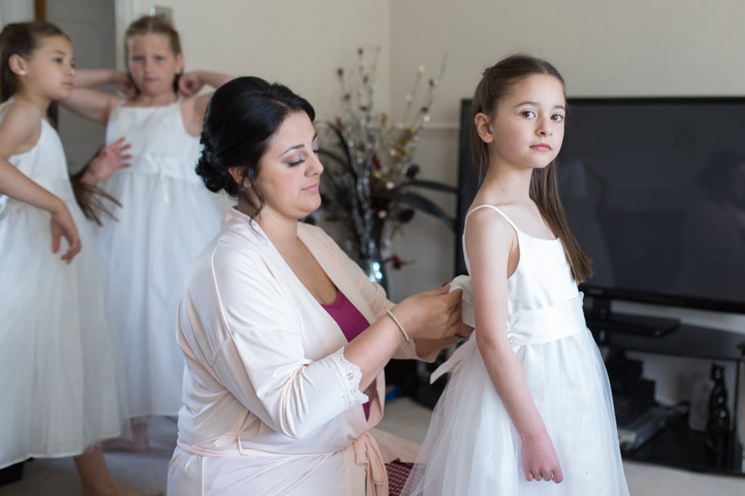 mother ties flower girl's dress bow
