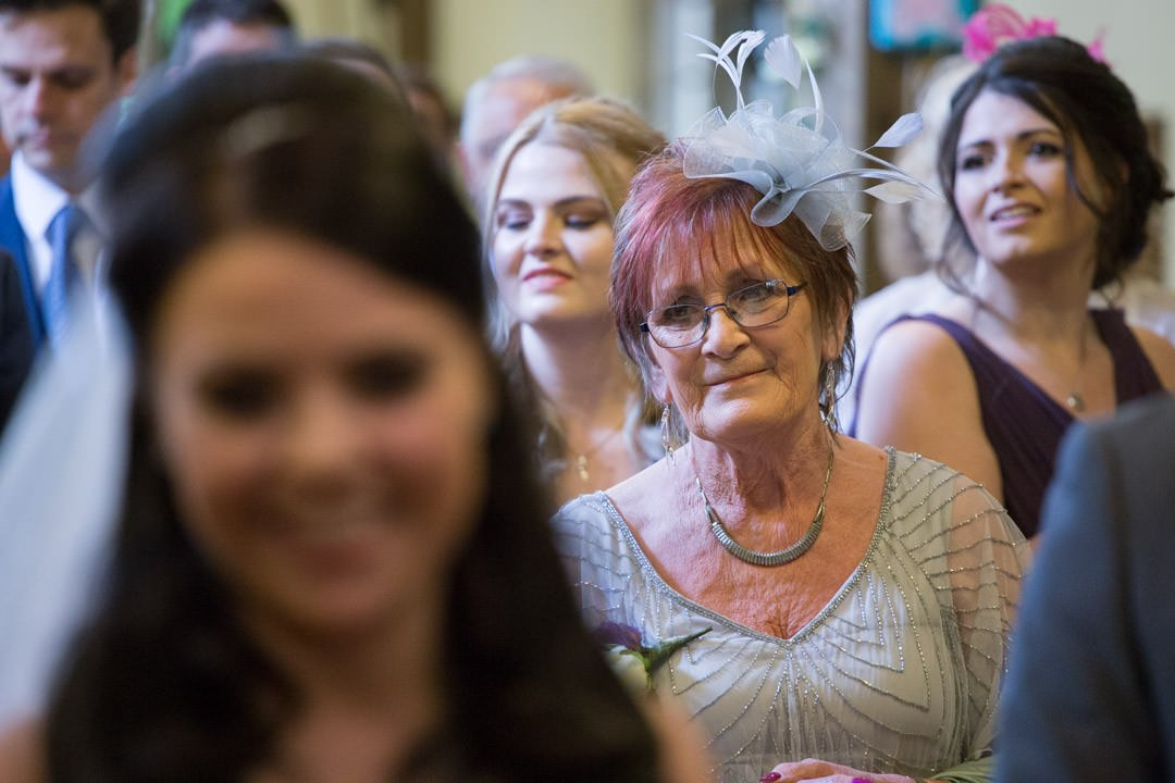 proud grandmother watches the bride in church