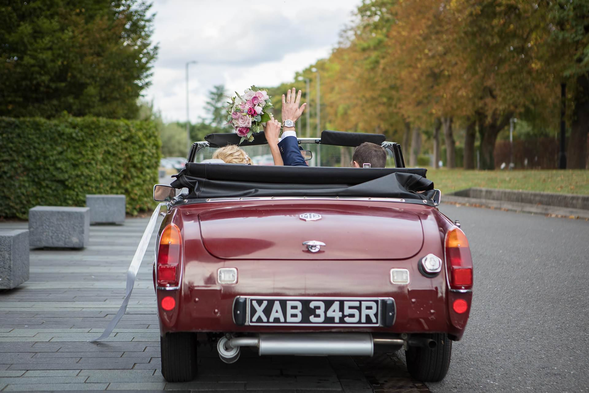 MG car leaves the Aviator, and the bride and groom wave goodbye