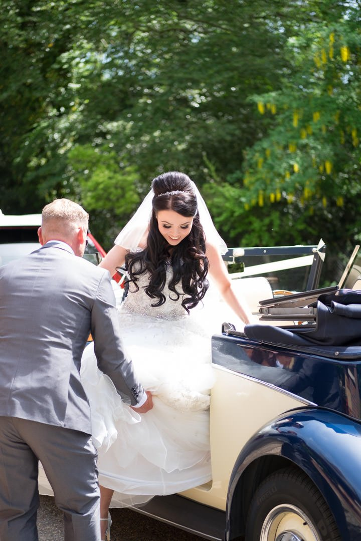 the bride gets out of the Rolls Royce Royale at church
