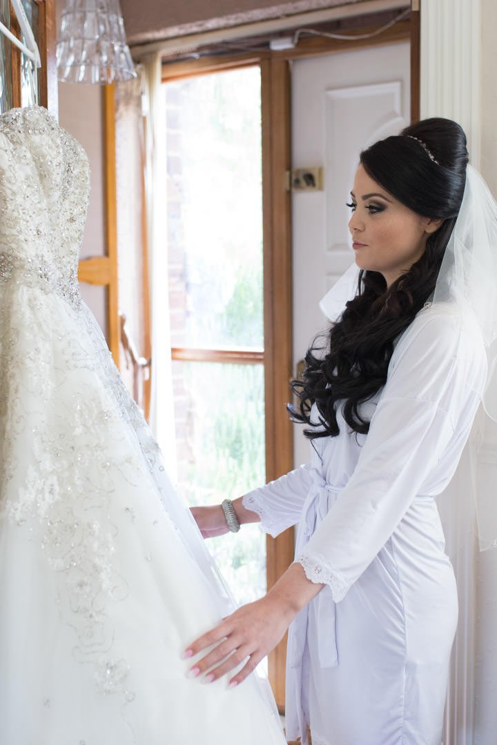 the bride checks over her wedding dress hanging on the door