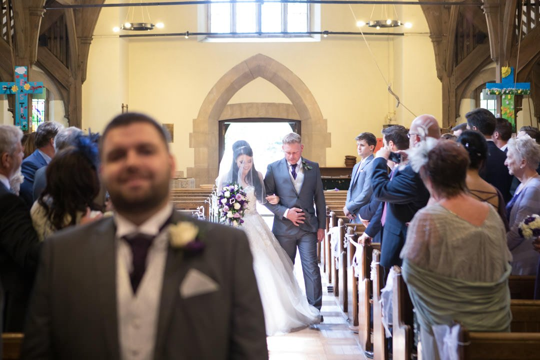 the bride walks down the aisle at St Andrew's church in Frimley Green