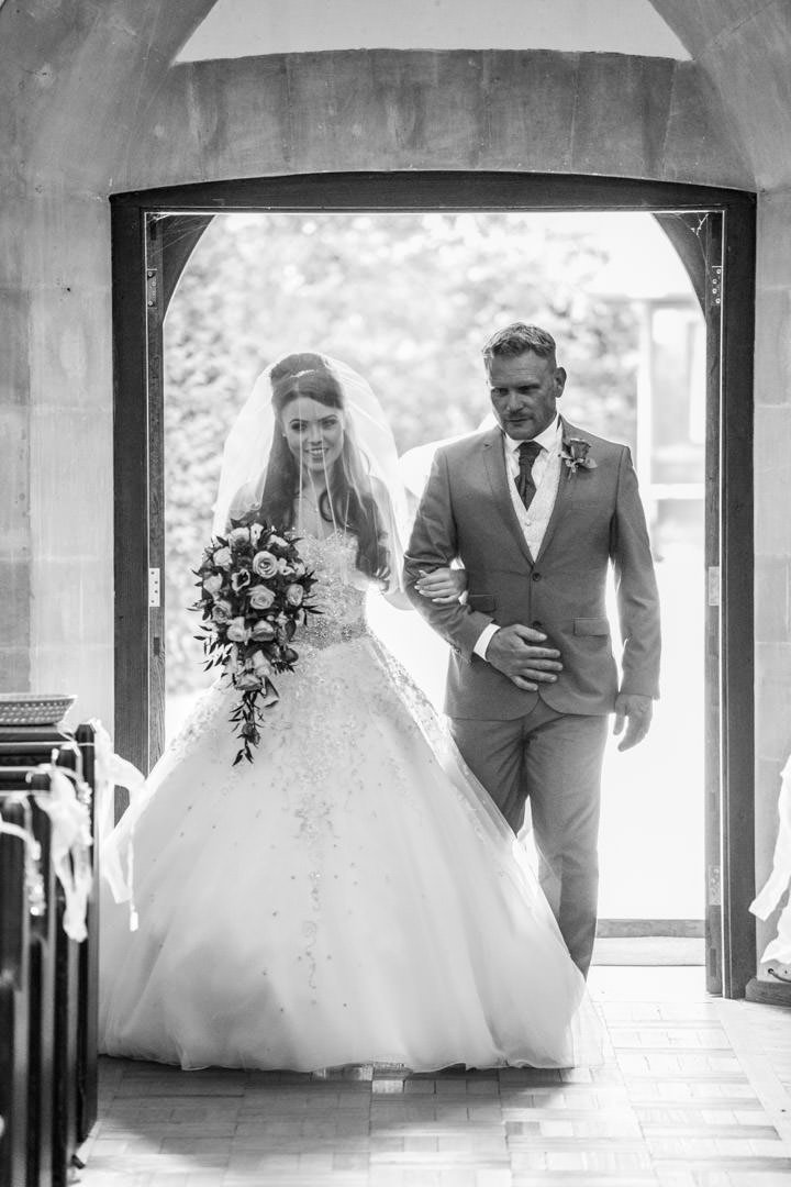 black and white of the bride walking in to St Andrew's church in Frimley Green with her uncle
