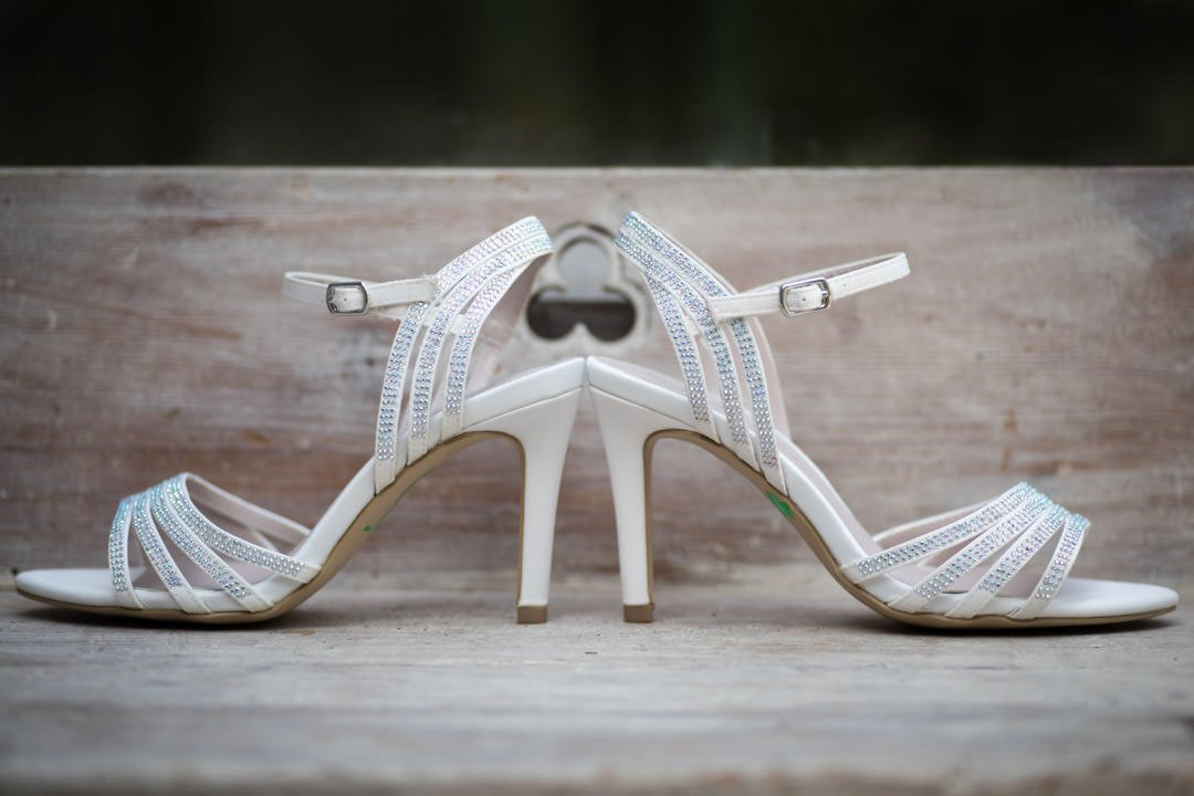 the bride's diamante studded white high heels on a wooden chest of drawers with a club cutout