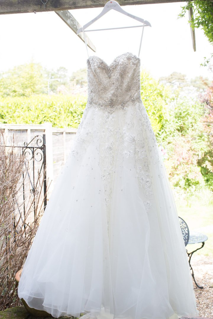 the bride's diamante and tulle wedding dress hangs from the pergola in the garden