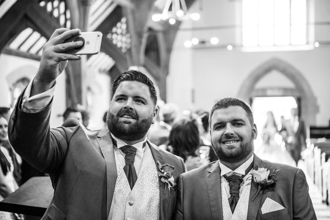 the groom and best man have a selfie as the bride walks down the aisle at St Andrew's church in Frimley Green