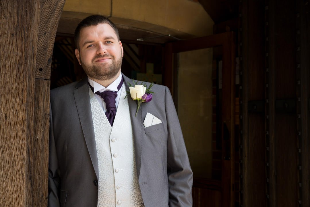 the groom wearing grey morning suit, purple cravat and buttonhole and cream waistcoat poses outside the St Andrew's church